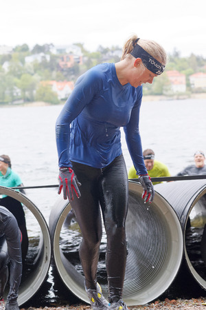 tough woman: STOCKHOLM, SWEDEN - MAY 14, 2016: Smiling woman coming out from a tube obstacle in the obstacle race Tough Viking Event in Sweden, May 14, 2016