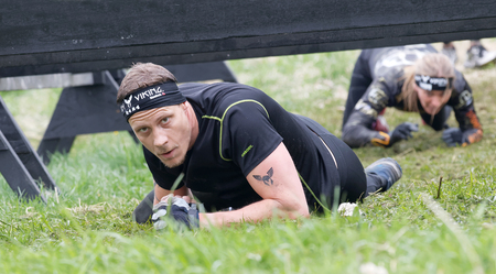 tough woman: STOCKHOLM, SWEDEN - MAY 14, 2016: Concentrated man with tatoo crawling below a barb wire obstacle, a woman behind in the obstacle race Tough Viking Event in Sweden, May 14, 2016 Editorial