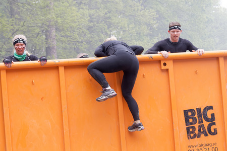 obstacle: STOCKHOLM, SWEDEN - MAY 14, 2016: Group of woman and men climbing a orage container obstacle in the obstacle race Tough Viking Event in Sweden, May 14, 2016