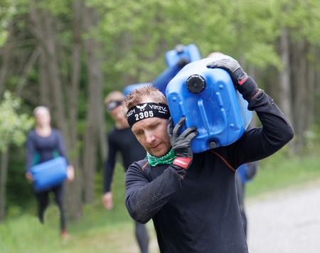 woman street: STOCKHOLM, SWEDEN - MAY 14, 2016: Group of woman and men carry a heavy water can in the forest in the obstacle race Tough Viking Event in Sweden, May 14, 2016