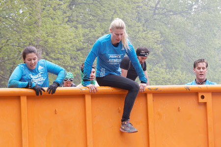 tough woman: STOCKHOLM, SWEDEN - MAY 14, 2016: Group of woman and men climbing a orage container obstacle in the obstacle race Tough Viking Event in Sweden, May 14, 2016