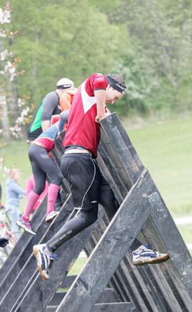 Estocolmo, Suecia - 14 de mayo, 2016: Las mujeres y los hombres que sube sobre una plancha de obstáculos en la carrera de obstáculos de Viking Tough Evento en Suecia, 14 de Mayo, el año 2016
