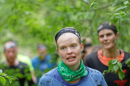 woman run: STOCKHOLM, SWEDEN - MAY 14, 2016: Blonde woman with blue eyes and mud in her face running in the forest in the obstacle race Tough Viking Event in Sweden, May 14, 2016 Editorial