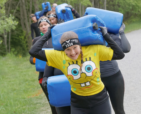 tough woman: STOCKHOLM, SWEDEN - MAY 14, 2016: Group of smiling woman and men carry a heavy water can in the forest in the obstacle race Tough Viking Event in Sweden, May 14, 2016