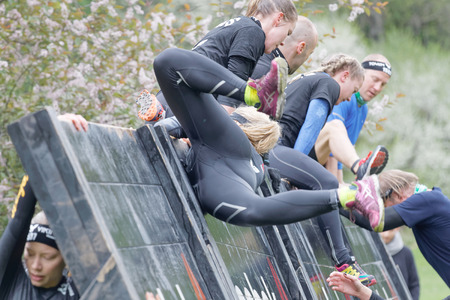 overturn: STOCKHOLM, SWEDEN - MAY 14, 2016: Women making a spectacular overturn when climbing over a plank obstacle in the obstacle race Tough Viking Event in Sweden, May 14, 2016 Editorial