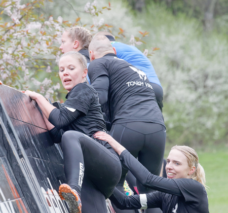 woman run: STOCKHOLM, SWEDEN - MAY 14, 2016: Smiling women climbing over a plank obstacle in the obstacle race Tough Viking Event in Sweden, May 14, 2016 Editorial