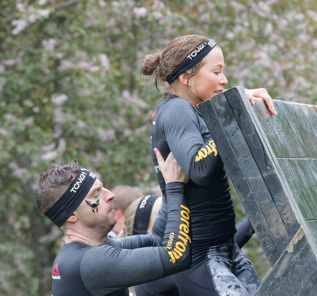 woman run: STOCKHOLM, SWEDEN - MAY 14, 2016: Man helping a women climbing over a plank obstacle in the obstacle race Tough Viking Event in Sweden, May 14, 2016 Editorial