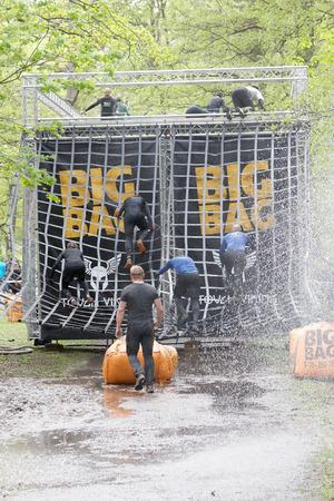 Estocolmo, Suecia - 14 de mayo, 2016: Grupo de hombres y mujeres que suben un obstáculo red, chorros de agua, en la carrera de obstáculos de Viking Tough Evento en Suecia, 14 de Mayo, el año 2016