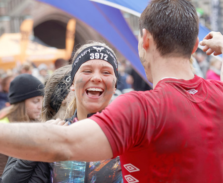dangerous love: STOCKHOLM, SWEDEN - MAY 14, 2016: Smiling man with mud in his face hugging a woman after finishing a race in the obstacle race Tough Viking Event in Sweden, May 14, 2016 Editorial