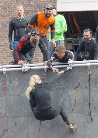 rampage: STOCKHOLM, SWEDEN - MAY 14, 2016: Woman climbing the rampage obstacle, hanging in rope and beeing helped in the obstacle race Tough Viking Event in Sweden, May 14, 2016
