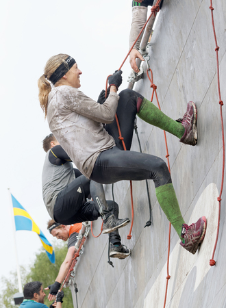 rampage: STOCKHOLM, SWEDEN - MAY 14, 2016: Two  woman climbing the rampage obstacle, hanging in rope  in the obstacle race Tough Viking Event in Sweden, May 14, 2016
