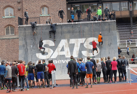 obstacle: STOCKHOLM, SWEDEN - MAY 14, 2016: Group of men and woman waiting to climb the rampage obstacle in the obstacle race Tough Viking Event in Sweden, May 14, 2016