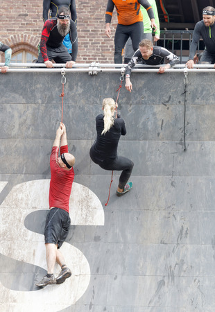 rampage: STOCKHOLM, SWEDEN - MAY 14, 2016: Group of men and woman climbing the rampage, hanging in rope obstacle in the obstacle race Tough Viking Event in Sweden, May 14, 2016 Editorial
