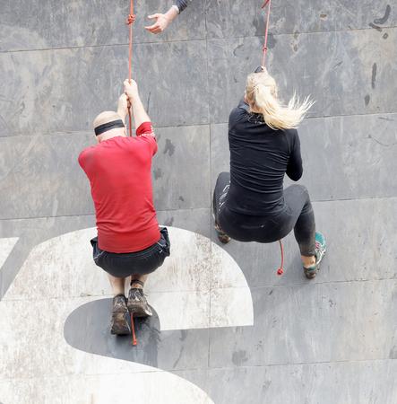 Estocolmo, Suecia - 14 de mayo, 2016: Grupo de los hombres y la mujer que sube al alboroto, que cuelgan en la cuerda obstáculo en la carrera de obstáculos Tough Evento de Viking en Suecia, 14 de Mayo, el año 2016 Editorial