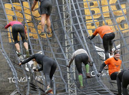 Estocolmo, Suecia - 14 de mayo, 2016: Vista trasera de un grupo de hombres y mujeres que suben un obstáculo neta en la carrera de obstáculos de Viking Tough Evento en Suecia, 14 de Mayo, el año 2016