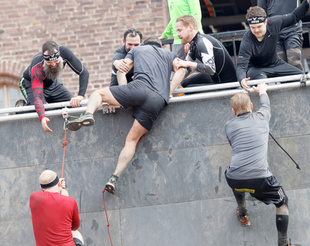 rampage: STOCKHOLM, SWEDEN - MAY 14, 2016: Group of men climbing the rampage obstacle, hanging in rope beeing helped  in the obstacle race Tough Viking Event in Sweden, May 14, 2016