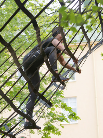 tough woman: STOCKHOLM, SWEDEN - MAY 14, 2016: Woman  climbing a net obstacle in the obstacle race Tough Viking Event in Sweden, May 14, 2016