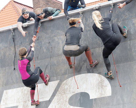obstacle: STOCKHOLM, SWEDEN - MAY 14, 2016: Three  woman climbing the rampage obstacle, hanging in rope and beeing helped in the obstacle race Tough Viking Event in Sweden, May 14, 2016