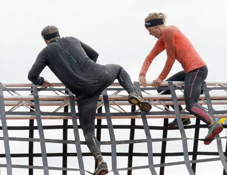 Estocolmo, Suecia - 14 de mayo, 2016: Vista trasera de la mujer y el hombre que sube un obstáculo neta en la carrera de obstáculos de Viking Tough Evento en Suecia, 14 de Mayo, el año 2016 Editorial