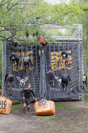 Estocolmo, Suecia - 14 de mayo, 2016: Grupo de hombres y mujeres que suben un obstáculo neta en la carrera de obstáculos de Viking Tough Evento en Suecia, 14 de Mayo, el año 2016 Editorial