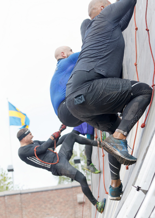 rampage: STOCKHOLM, SWEDEN - MAY 14, 2016: Group of men climbing the rampage obstacle, hanging in rope  in the obstacle race Tough Viking Event in Sweden, May 14, 2016