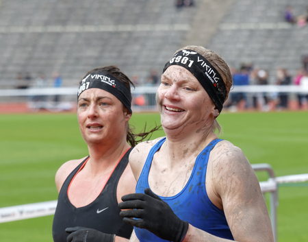 tough woman: STOCKHOLM, SWEDEN - MAY 14, 2016: Two senior happy woman running in the obstacle race Tough Viking Event in Sweden, May 14, 2016 Editorial