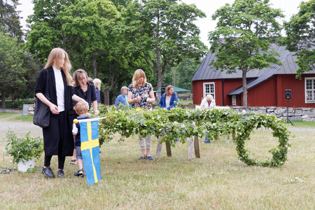 midsummer pole: VADDO, SWEDEN - JUNE 23, 2016: Woman and children making the maypole making the maypole before raising it, celebrating the Midsommer in Sweden, June 23, 2016