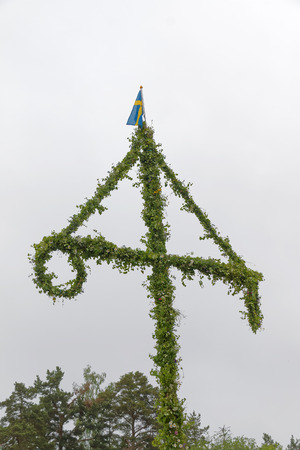 midsummer pole: The Maypole, white sky in the background, celebrating the Midsommer in Sweden, June 23, 2016