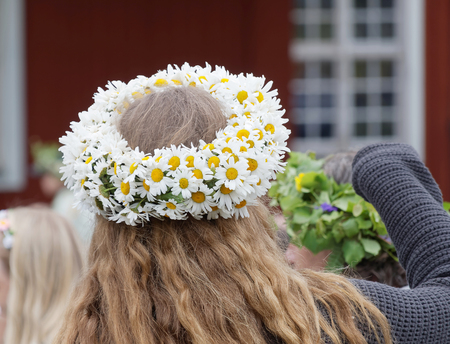 midsummer pole: VADDO, SWEDEN - JUNE 23, 2016: Woman with oxeye daisy flowers in her hair during the traditional celebration of the Midsummer in Sweden, June 23, 2016