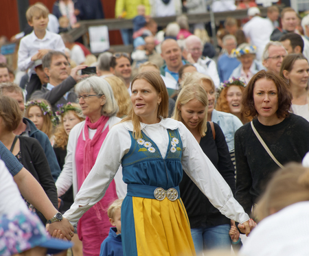 VADDO, SWEDEN - JUNE 23, 2016: Dancing woman wearing traditional swedish costume dancing around the the maypole, celebrating the Midsummer in Sweden, June 23, 2016