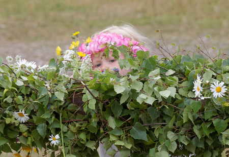 midsummer pole: VADDO, SWEDEN - JUNE 23, 2016: Litte girl wearing flowers in the hair making the maypole, celebrating the Midsommer in Sweden, June 23, 2016