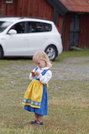 midsummer pole: VADDO, SWEDEN - JUNE 23, 2016: Litte girl wearing  traditional costume before the traditional dancing around the the maypole, celebrating the Midsummer in Sweden, June 23, 2016 Editorial