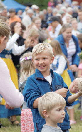 midsummer pole: VADDO, SWEDEN - JUNE 23, 2016: Smiling young blonde boy dancing around the the maypole, celebrating the Midsummer in Sweden, June 23, 2016
