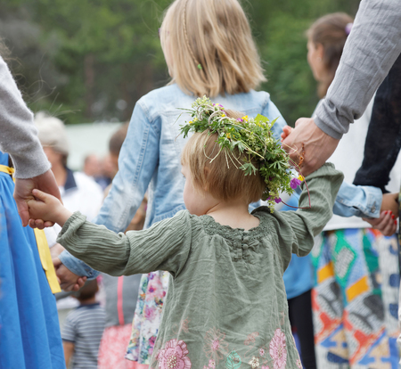 midsummer pole: VADDO, SWEDEN - JUNE 23, 2016: Litte girl wearing flowers in the hair dancing around the maypole, celebrating the Midsummer in Sweden, June 23, 2016 Editorial