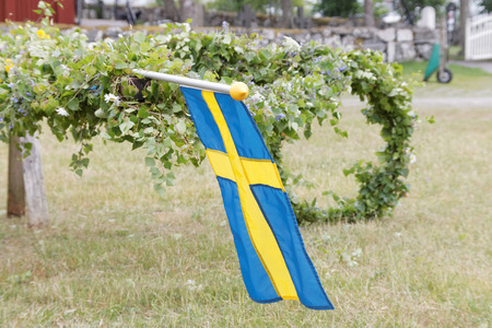 midsummer pole: VADDO, SWEDEN - JUNE 23, 2016: Maypole with leaf and swedish flag before raising it, celebrating the Midsommer in Sweden, June 23, 2016 Editorial