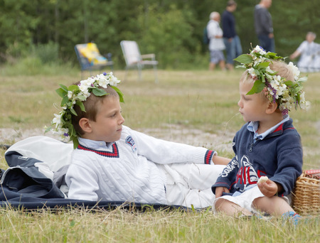 midsummer pole: VADDO, SWEDEN - JUNE 23, 2016: Two young boys with flowers in the hair laying on the grass, celebrating the Midsommer in Sweden, June 23, 2016
