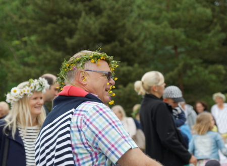 VADDO, SWEDEN - JUNE 23, 2016: Smiling senior man with flowers in the hair dancing around the the maypole, celebrating the Midsummer in Sweden, June 23, 2016