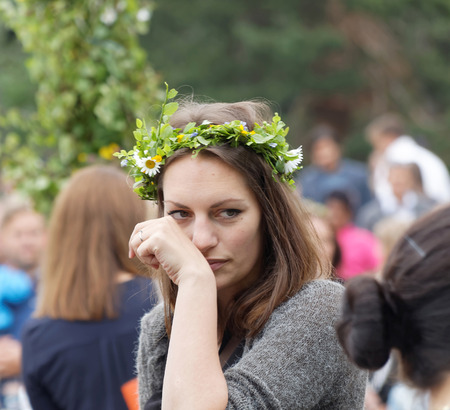 midsummer pole: VADDO, SWEDEN - JUNE 23, 2016: Woman with flowers in her hair, maypole in the background during the traditional dance, celebrating the Midsommer in Sweden, June 23, 2016