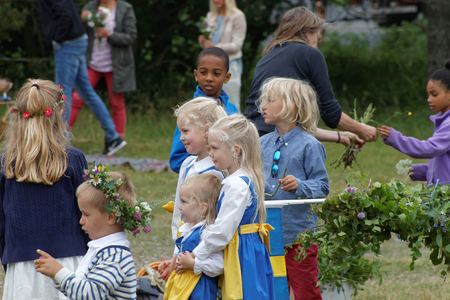 midsummer pole: VADDO, SWEDEN - JUNE 23, 2016: Children wearing traditional costume and flowers in the hair making the maypole, celebrating the Midsommer in Sweden, June 23, 2016