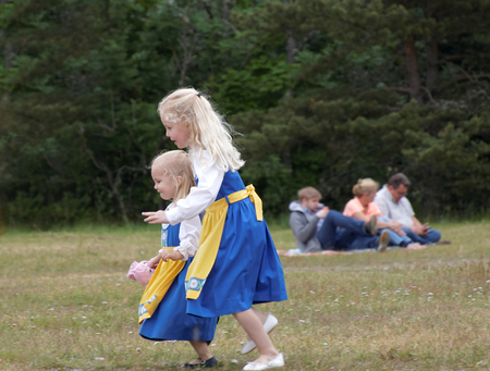 midsummer pole: VADDO, SWEDEN - JUNE 23, 2016: Smiling children wearing traditional costume running on the grass, celebrating the Midsommer in Sweden, June 23, 2016