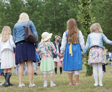 midsummer pole: VADDO, SWEDEN - JUNE 23, 2016: Children and adults dancing around the Maypole, celebrating the Midsummer in Sweden, June 23, 2016