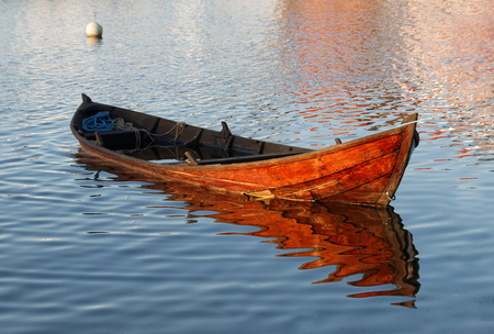 to get warm: Wooden rowboat in warm evening light partly filled with water to get it waterproof