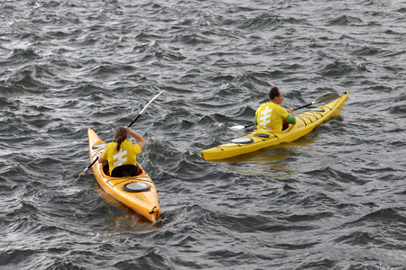 woman squirt: STOCKHOLM - JUL 02, 2016: Yellow canoes with officials before the start signal in the Womens ITU World Triathlon series event July 02, 2016 in Stockholm, Sweden