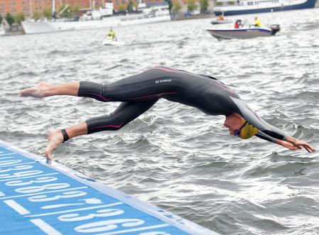 STOCKHOLM - 2. JULI 2016: Weiblicher Schwimmer, der in das Wasser im Welt-Triathlon-Reihenereignis der Frauen ITU am 2. Juli 2016 in Stockholm, Schweden springt