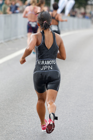 STOCKHOLM - JUL 02, 2016: Rear view of triathlete Aoi Kuramoto running in the rain in the Womens ITU World Triathlon series event July 02, 2016 in Stockholm, Sweden
