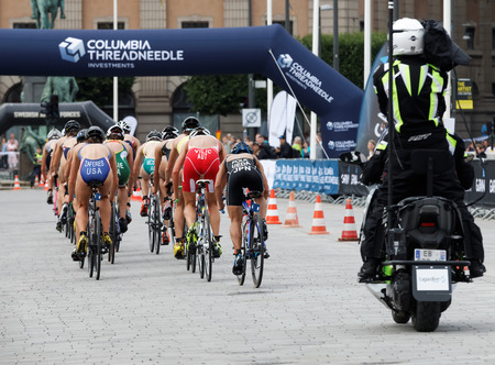 STOCKHOLM - JUL 02, 2016: Rear view of large group of triathlete cyclists Zaferes, Ueda, Vilic andcompetitors in the Womens ITU World Triathlon series event July 02, 2016 in Stockholm, Sweden Editorial