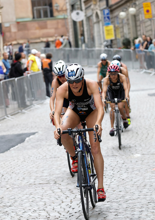 STOCKHOLM - JUL 02, 2016: Simone Ackermann and group of female triathlete cyclists cycling downhill on cobblestone in the Womens ITU World Triathlon series event July 02, 2016 in Stockholm, Sweden
