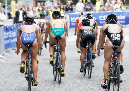 ide: STOCKHOLM - JUL 02, 2016: Rear view of colorful group of triathlete cyclists Zaferes, Van Coevorden, Ueda, Ide and audience in the Womens ITU World Triathlon series event July 02, 2016 in Stockholm, Sweden Editorial