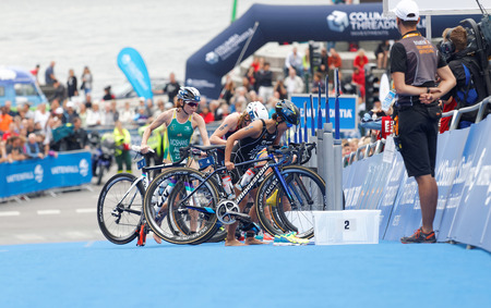 cycles: STOCKHOLM - JUL 02, 2016: Group of triathletes parking cycles in the transition zone in the Womens ITU World Triathlon series event July 02, 2016 in Stockholm, Sweden