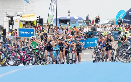 ciclos: ESTOCOLMO - JUL 02, 2016: Grupo de los triatletas que se ejecuta con los ciclos en la zona de transición en la prueba de las series mundiales de la UIT Triatlón de la Mujer 02 de julio de, 2016, Estocolmo, Suecia